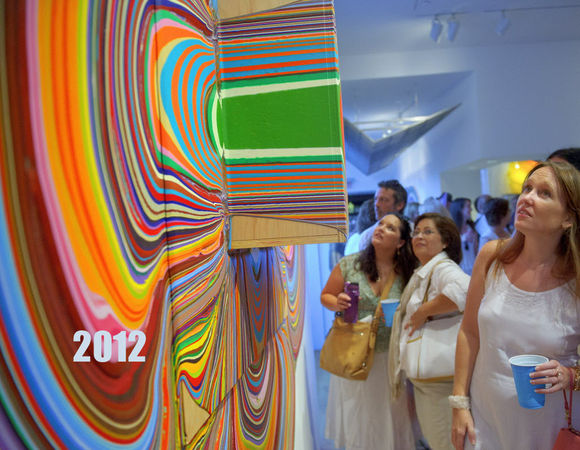 """MATTHEW HINTON / THE TIMES-PICAYUNE Stephanie Dovalina, center, background, her mother Monica Dovalina, and friend Kristen Nygren, foreground right, look at the work of Holton Rower called """"Love Heals"""" at the Arthur Roger gallery on Julia Street during White Linen Night in New Orleans, La., Saturday, Aug. 4, 2012. The painting technique involves pouring successive quantities of modified paint onto plywood. The paint, sometimes mixed with reflective or opalescent elements, flows slowly and determinedly over the surfaces resulting in amorphous shapes. The works vary from an inch thick to including protrusions called """"hats"""" that extend out by a foot. Other paintings feature """"exclusions"""", points where the artist placed obstacles that were later removed, forcing the paint to change direction."""