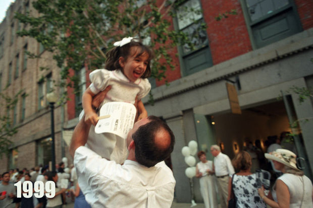 STAFF PHOTO BY JENNIFER ZDON Vittorio Colangelo tosses his friend's daughter Margaret Saux, 6, into the air outside of the Heriard-Cimino Gallery on Julia St. during White Linen Night Saturday, August 7, 1999 which is held throughout the Warehouse Arts District and included music, food and open several galleries.