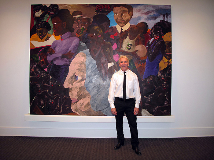 New Orleans gallerist Arthur Roger with a Robert Colescott painting at his gallery