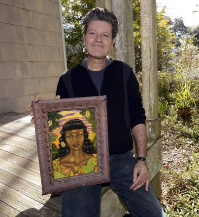 Advocate Staff Photo by Bill Feig - Douglas Bourgeois holds a 2001 painting of his, 'Woman with Lady Beetles' on his front porch. Bourgeois, a painter who lives in St. Amant, LA, near Gonzales, is a Prospect.3 artist.