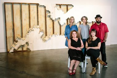 """Clockwise from top left, Sidonie Villere, Courtney Egan, Carl Joe Williams, Carlie Trosclair and Stephanie Patton in front of Ms. Trosclair's """"Fissure?"""" at the Contemporary Arts Center in New Orleans. William Widmer for The New York Times"""