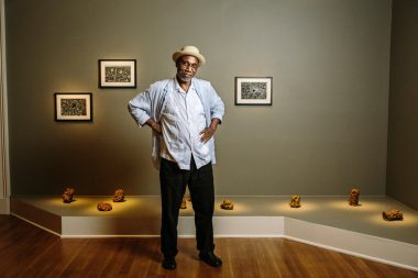 """Willie Birch with his """"Crawfish Dwelling"""" sculptures and """"Wildflowers or Dwelling"""" drawings at the New Orleans Museum of Art. William Widmer for The New York Times"""