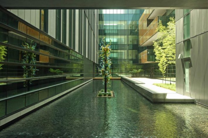 """Glass artist Dale Chihuly's """"Crystal Blue and Amber Tower"""" (2015) was placed over a stone-lined reflecting pond in the medical center. [Photo by John D'Addario]"""